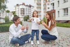 在新的公寓前面的愉快的家庭 免版税库存图片