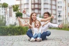 在新的公寓前面的愉快的家庭 库存图片