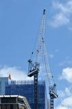 在新的公寓的起重机工作阻拦建造场所 免版税库存图片