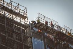 在新的大厦建筑工作的工作者 免版税图库摄影