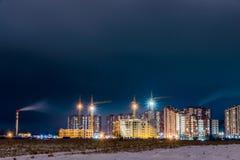 在新的大厦的夜视图在城市的郊区从荒地的 库存照片