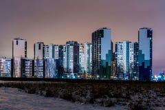在新的大厦的夜视图在城市的郊区从荒地的 库存图片