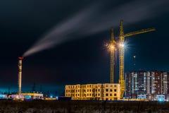 在新的大厦的夜视图在城市的郊区从荒地的 图库摄影