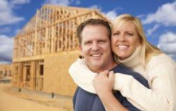 在新的家庭建筑构筑的站点前面的夫妇 库存图片