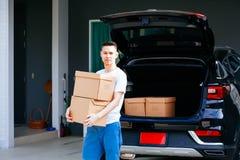 在新的家成熟亚裔从车厢的人运载的纸板箱 库存图片