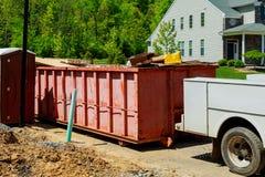 在新的家附近的垃圾容器,红色容器,回收和废建造场所背景的 图库摄影