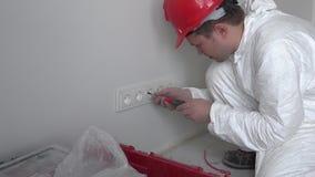 在新的平的房屋建设公寓的专业人登上壁上插座出口 影视素材