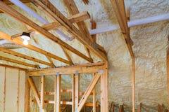 在新的木屋倾斜的天花板安装的泡沫塑料绝缘材料  免版税库存照片