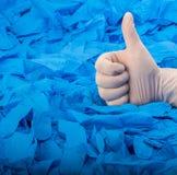 在新的白色乳汁医疗手套的手在很蓝色橡胶手套背景  免版税库存图片