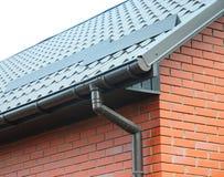 在新的雨天沟系统和屋顶保护的特写镜头免受雪板(雪卫兵) 免版税图库摄影