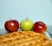在新近地做的苹果饼旁边的三个苹果; 库存图片