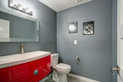 在新近地被更新的灰色和红色卫生间设计在家 图库摄影