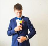 在新郎服装的美妙的婚礼钮扣眼上插的花  库存图片