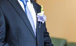 在新郎特写镜头服装的美妙的婚礼钮扣眼上插的花  免版税库存照片