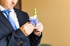 在新郎特写镜头服装的美妙的婚礼钮扣眼上插的花  库存图片
