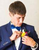 在新郎特写镜头服装的美妙的婚礼钮扣眼上插的花  免版税库存图片