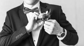 在新郎特写镜头服装的美妙的婚礼钮扣眼上插的花  免版税图库摄影