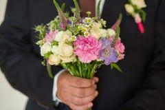 在新郎现有量的婚礼花束 免版税库存图片