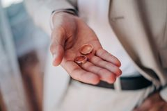 在新郎的手上,他的棕榈的,谎言两金子婚戒 免版税库存照片