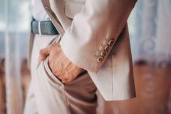在新郎` s婚礼衣服穿戴的胳膊被卷起入支持皮带裤子的口袋 免版税库存照片