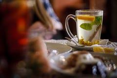 在新鲜的叶子外面的新作薄荷的茶在黑暗的背景 免版税库存照片
