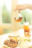 在新鲜的奶蛋烘饼的蜂蜜 免版税图库摄影