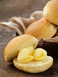 在新鲜的小圆面包面包的黄色牛奶店黄油 免版税图库摄影