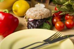 在新鲜的成份和板材旁边的健康汉堡 图库摄影