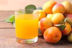 在新鲜的杏子旁边的杏子汁在棕色木背景 免版税库存图片
