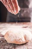 洒在新鲜的温暖的面包的贝克手面粉 图库摄影