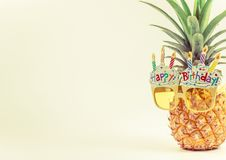 在新鲜的菠萝,在左边,夏天生日概念,淡色的拷贝空间的黄色花梢玻璃 图库摄影