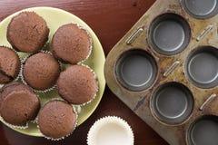 在新鲜的被烘烤的巧克力杯子上的平的位置在有烘烤盘子的板材结块在背景中 免版税图库摄影