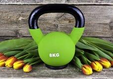 在新鲜的郁金香之间的现代kettlebell在土气木桌上 免版税库存图片