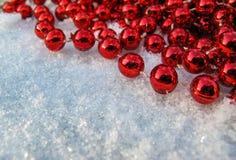 在新鲜的雪背景的角落的红色小珠  免版税库存图片