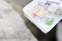 在新鲜空气的土耳其快乐糖lukum在以海为背景的包裹 红色和绿色 免版税库存图片