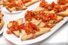 在新鲜面包,作为顶部的pesto的水多的蕃茄 免版税库存图片