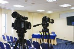 在新闻招待会,事件,新闻工作者,会议期间专业摄象机在三脚架登上记录录影 库存照片