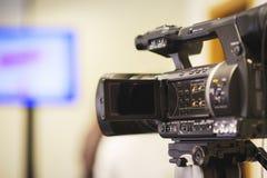 在新闻招待会,事件,新闻工作者,会议期间专业摄象机在三脚架登上记录录影 免版税库存照片
