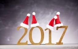 在新年2017数字的四个圣诞老人帽子 免版税库存照片