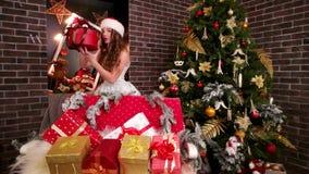 在新年` s室全部孩子的明亮的惊奇,圣诞老人` s帽子的女孩拿着红色欢乐箱子,美丽的女孩 股票视频