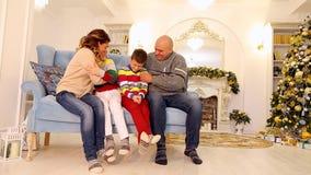 在新年` s心情的友好的家庭一起获得乐趣,坐蓝色沙发在有圣诞树的欢乐装饰的室 股票视频