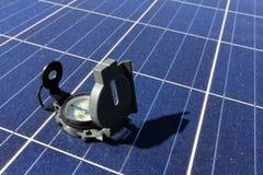在方向概念的太阳电池板重要性的指南针 免版税图库摄影