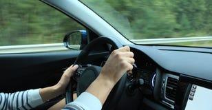 在方向盘的不正确手位置在快行车里面 库存图片