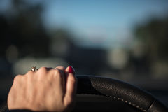 在方向盘的女性手 免版税库存照片