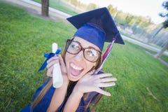 在方帽与长袍的愚蠢的青少年的女性举行的文凭 免版税图库摄影