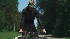 在方形字体自行车的年轻人驱动在乡下公路 影视素材