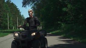 在方形字体自行车的年轻人驱动在乡下公路 股票录像