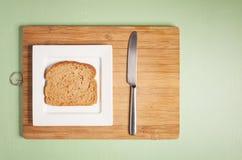 在方形的白色板材的切的黑面包有刀子的 图库摄影