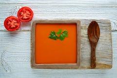 在方形的盘和白色木头的西红柿酱 库存照片
