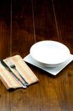 在方形的盘的空的在家庭用亚麻布的碗与叉子和刀子 免版税图库摄影